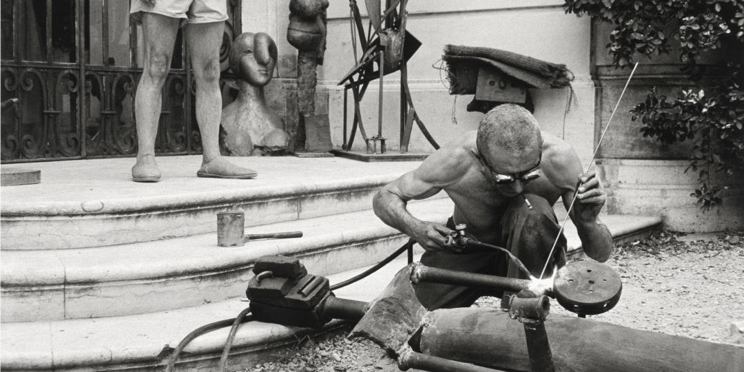 "Worker welding ""Woman with Key"", known as ""The Jailer"", in front of the entrance to La Californie, Cannes, in 1957 by David Douglas Duncan"