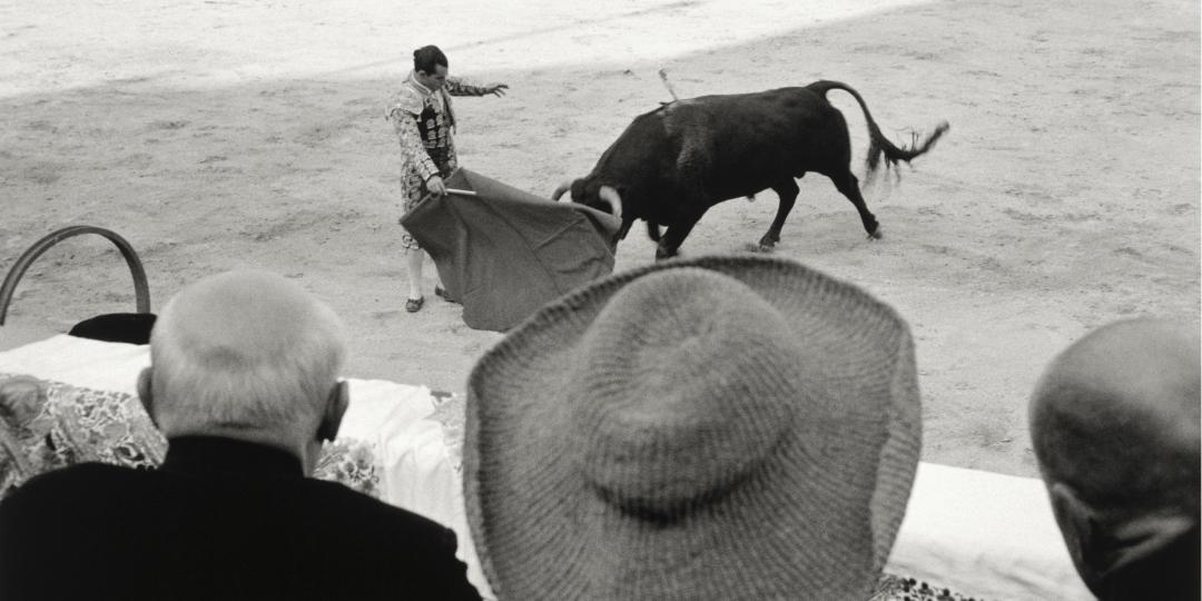 Pablo Picasso, Jacqueline Roque and Michel Leiris from the back in the grandstands of the Arles Amphitheatre, in 1957 by David Douglas Duncan