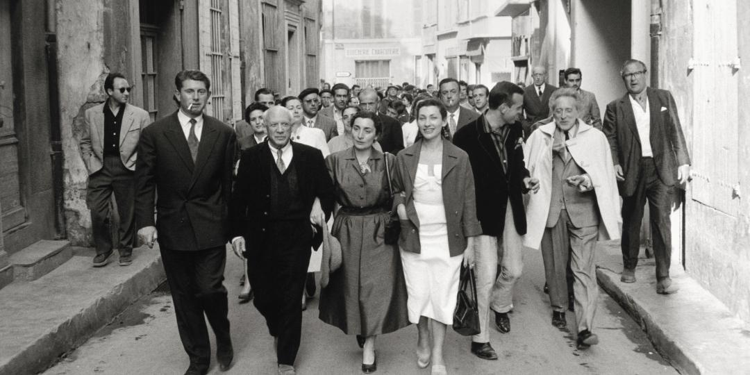 Paulo Picasso, Pablo Picasso, Jacqueline Roque, Christine Picasso, John Richardson, Jean Cocteau, David Cooper followed by Michel Leiris on the way to the Corrida, on the streets of Arles, in 1957 by David Douglas Duncan